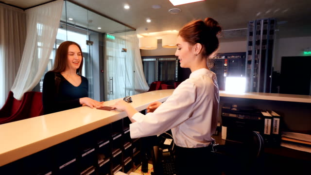 Lobby receptionist meeting business woman at hotel reception. 4K.