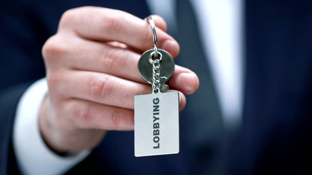 Lobbying word on keychain in male politician hand, governmental influence