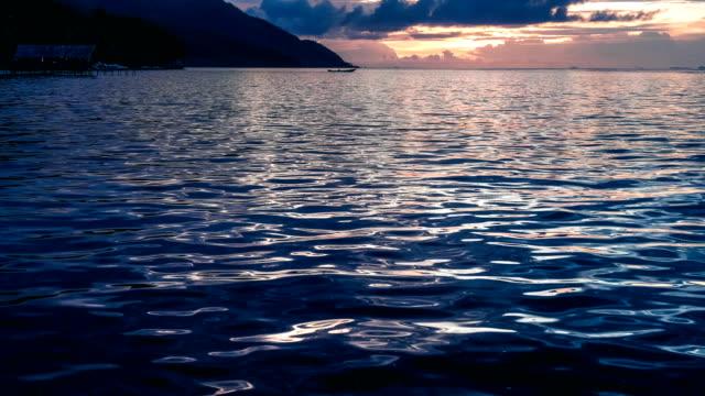 lokalen boot vom pier während des sonnenuntergangs über kri und monsuar verlassen. ruhigen wellen glitzern auf der meeresoberfläche, west-papua, raja ampat, indonesien - ewigkeit stock-videos und b-roll-filmmaterial