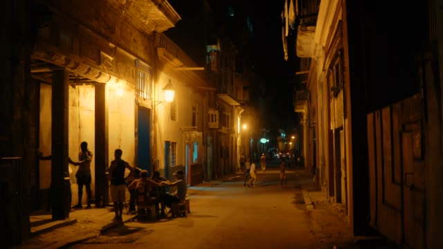 Local people relaxing and socializing in the streets of Havana old town at night Local people relaxing and socializing in the streets of Havana old town at night alley stock videos & royalty-free footage