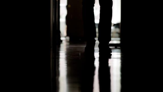 vidéos et rushes de tir rétroéclairé de verrouillage de l'homme d'affaires méconnaissable marchant en bas du couloir de bureau vers l'appareil-photo dans le plan lent, plan rapproché bas d'angle - ombre