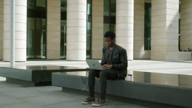 lockdown wide shot of african american young man sitting on stone seat outdoors and typing on his laptop computer - grandangolo tecnica fotografica video stock e b–roll