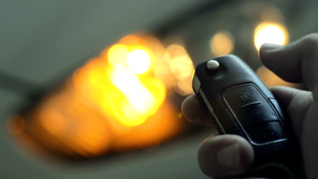 Locking and unlocking the car by the car's key remote control. Locking and unlocking the car by the car's key remote control. Pressing the button of the car key and the lights of the car blink when it's open or closed. car key stock videos & royalty-free footage