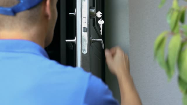 locksmith in blue uniform installing new house door lock