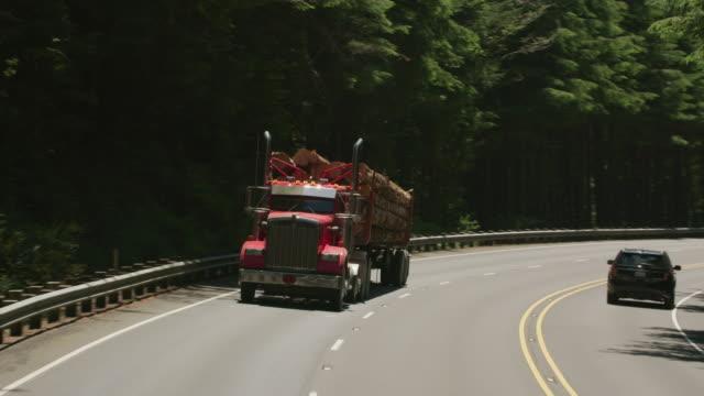 stockvideo's en b-roll-footage met vrachtwagen rijden op snelweg in oregon bos vastleggen - boomstam
