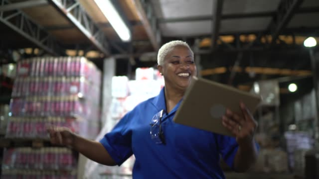 Logistics employee dancing at warehouse