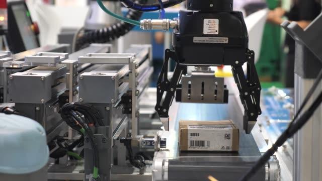 logistics robot arc catching a parcel for delivery - манипулятор робота производственное оборудование стоковые видео и кадры b-roll