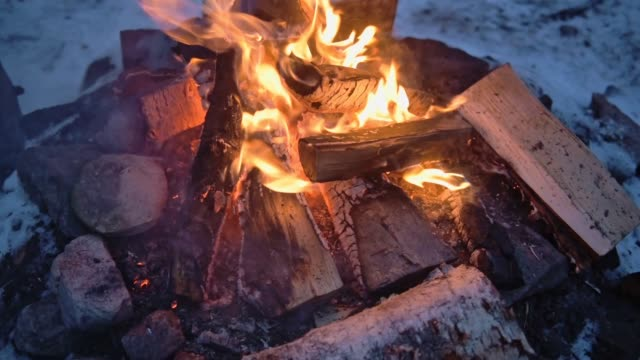 logs burning in a outdoor campfire, surrounded by snow, on a windy evening in lapland, finland - ice on fire video stock e b–roll