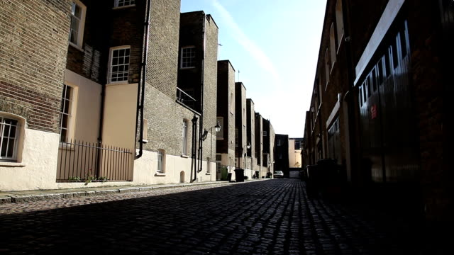 London mews street with cobbles A traditional mews (back street) in central London with cobblestone road. The road and buildings probably date back to Victorian times. alley stock videos & royalty-free footage