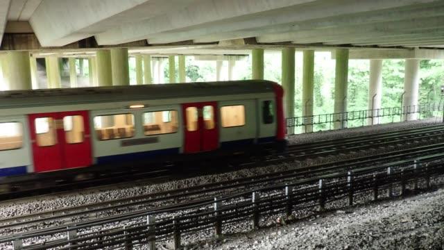 London Underground train passing underneath M25 Motorway bridge, Chorleywood, Hertfordshire video