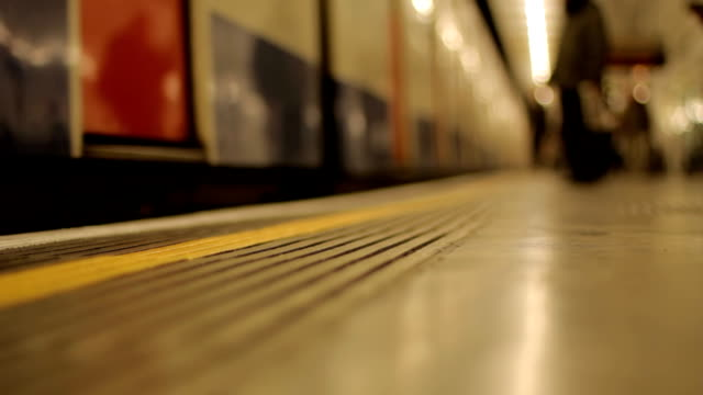 London Underground Selective focus as a London underground train stops at a platform and passengers embark and disembark. underground stock videos & royalty-free footage