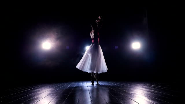 A lone ballerina in a long flowing skirt performs in the dark. 4K. video