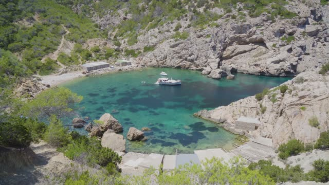 vídeos de stock e filmes b-roll de lone boat in a rocky inlet in ibiza - ibiza