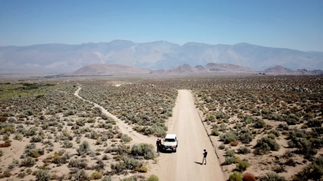 Lone Car Parked on Dirt Road in Desert Valley video