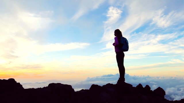 Lone female at sunset celebrates achieving her mountain hike above the clouds video