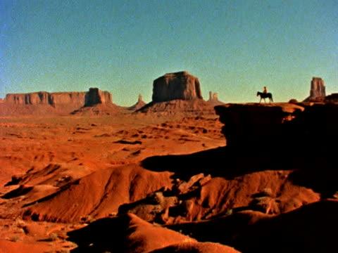 stockvideo's en b-roll-footage met lone horseback rider at monument valley - natuurgrond