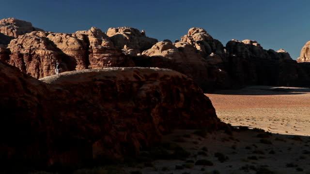 stockvideo's en b-roll-footage met eenzame man wandelen in wadi rum, vallei van de maan, jordanië - maasvallei