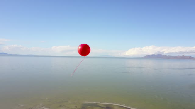 Lone red balloon floating high over the great salt lake video