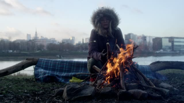 Lone woman burning campfire on a riverside