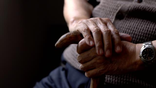 自宅の暗い部屋に座って杖と孤独年配の男性の手 - 介護点の映像素材/bロール