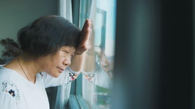 loneliness senior woman by window