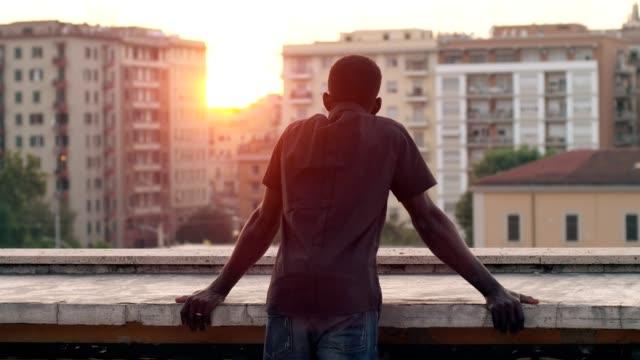 屋根を探して孤独なアフリカ人街バックに沈む夕日を見る - 屋根点の映像素材/bロール