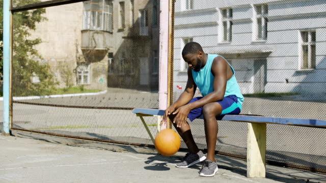 ensam afro-american sportsman sitter på bänken och leka med boll, sorg - bänk bildbanksvideor och videomaterial från bakom kulisserna