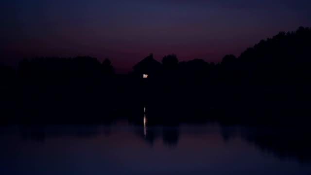 vídeos de stock e filmes b-roll de solitário ascetic casa no lago à noite - isolated house, exterior