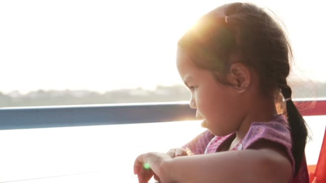 Lonely asian child girl feeling depressed and sleepy while sitting on boat with sunlight in slow motion shot video