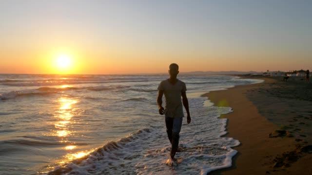 vídeos y material grabado en eventos de stock de atractivo joven africano solitario caminando por la playa al atardecer - moda playera