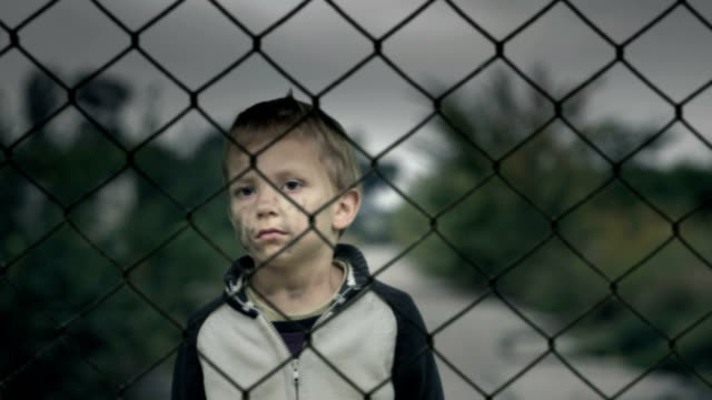 Lonely boy behind a fence, an orphan or refugee camp.