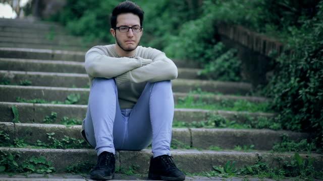 vídeos de stock e filmes b-roll de rapaz solitário na escada e a pensar em algum problema :  triste, mal- estar, sensação de peso no estômago - criança perdida