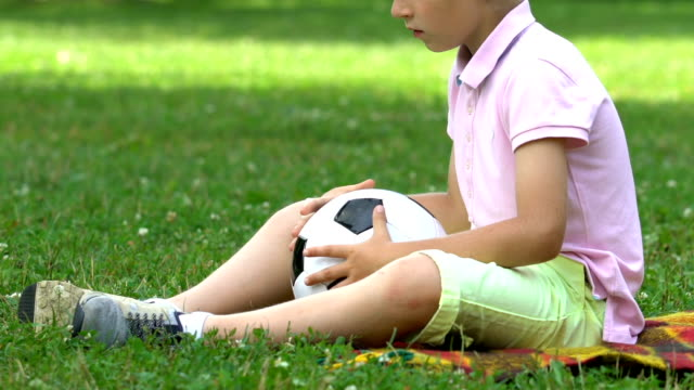 Lonely boy sitting in park with ball, no friends to play with, bullying problem Lonely boy sitting in park with ball, no friends to play with, bullying problem autism stock videos & royalty-free footage