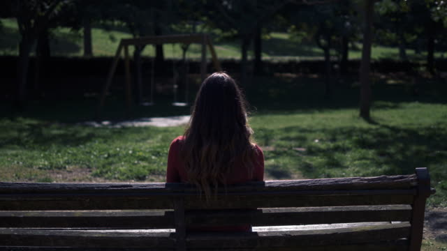 lonely brunette sit on bench standing up and walking away-back view - bench stock videos & royalty-free footage