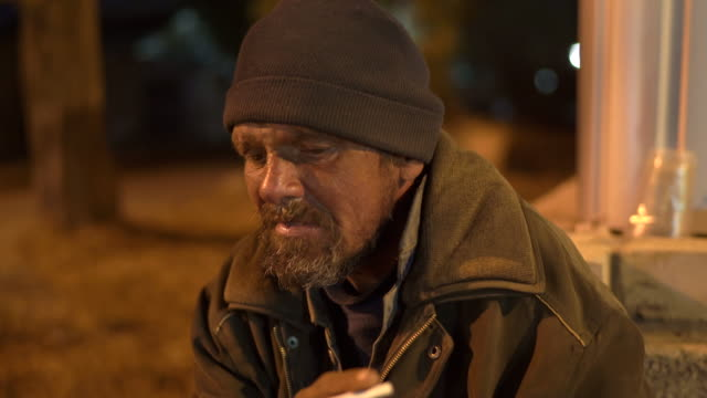 Lonely cold homeless man sitting on the street at night smoking cigarette. Lonely cold homeless man sitting on the street at night smoking cigarette. homeless person stock videos & royalty-free footage