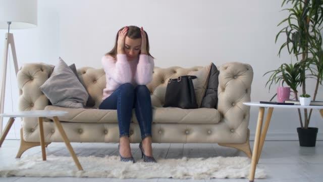 自宅のソファーに座っている孤独な落ち込んでいる大人の女性 - ソファ 女性点の映像素材/bロール