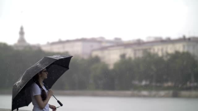 vídeos de stock, filmes e b-roll de garota solitária fica sob um guarda-chuva em tempo chuvoso, ao lado de um rio e pensa em alguma coisa - setembro amarelo