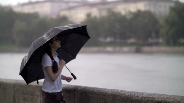 lonely girl stands under an umbrella in rainy weather beside a river and thinks about something