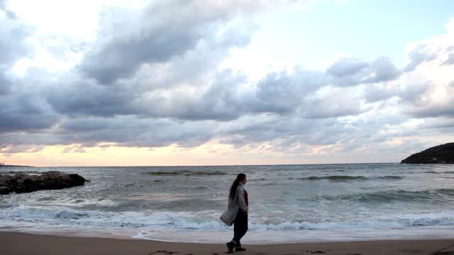 Lonely girl walking, empty beach video