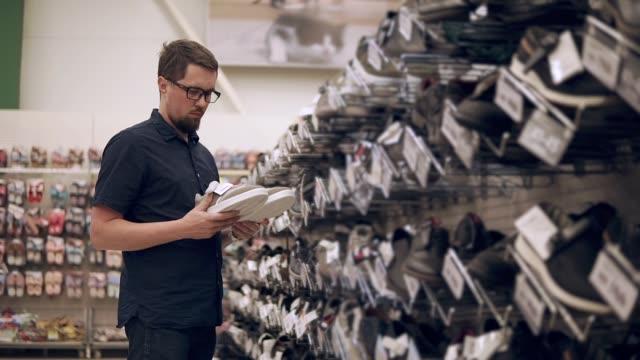 stockvideo's en b-roll-footage met eenzame man, het kopen van schoenen. - running shoes