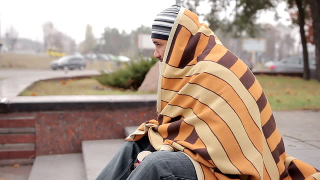 Lonely homeless man covered with shabby blanket feeling cold, asking for money video