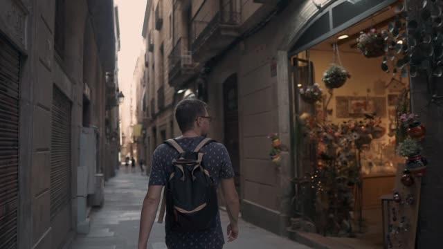 einsame männliche touristen ist ein spaziergang auf der alten straße, blick auf souvenir-shop - antique shop stock-videos und b-roll-filmmaterial