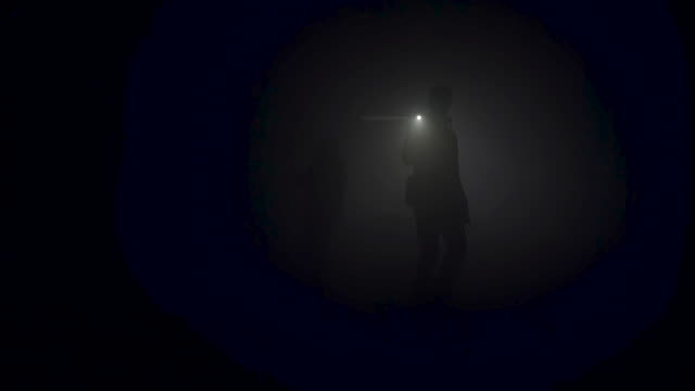 a lonely man exploring deep dark cave. stock footage. silhouette of a person standing inside of the cave on the background of the mystical moonlit - кейвинг стоковые видео и кадры b-roll