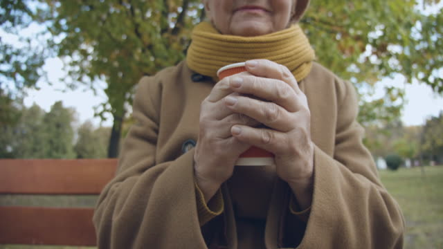 lonely old lady sitting in park with cup of hot beverage in hands, needs care - садовая скамья стоковые видео и кадры b-roll