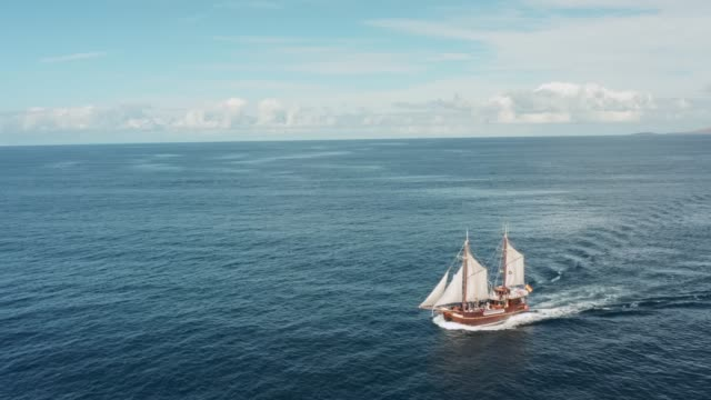 A lonely old pirate ship with white sails glides over the waves on the open sea in clear weather with a favorable wind