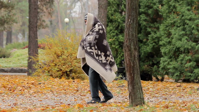 Lonely poor man limping in park, strange man covered with blanked needs help video