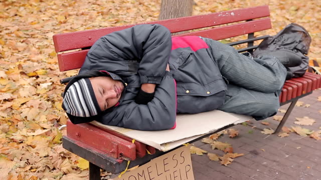 Lonely poor man lying on bench, miserable bum suffering from hunger and cold video