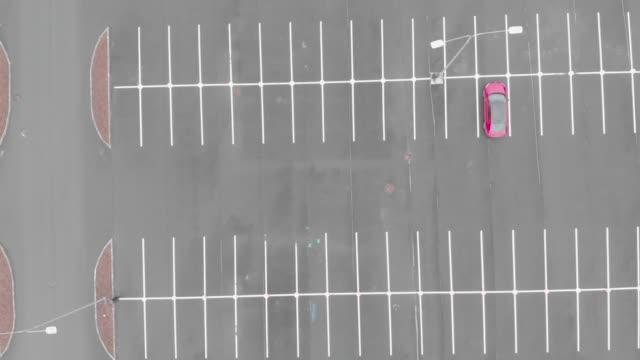 одинокая красная машина на пустой стоянке, воздушный выстрел. концепция борьбы с коронавирусом. - space background стоковые видео и кадры b-roll