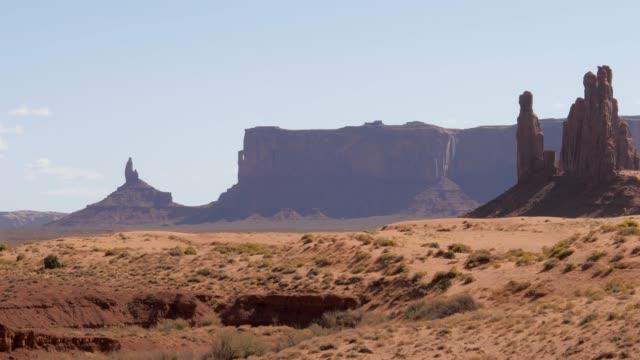 einsame felssäulen buttes of red sandsteformationen in monument valley usa - hochplateau stock-videos und b-roll-filmmaterial