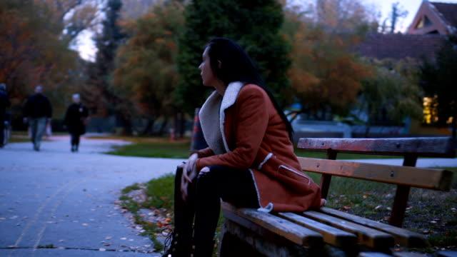 einsame, traurige frau standortwahl auf der bank - schwarzes haar stock-videos und b-roll-filmmaterial
